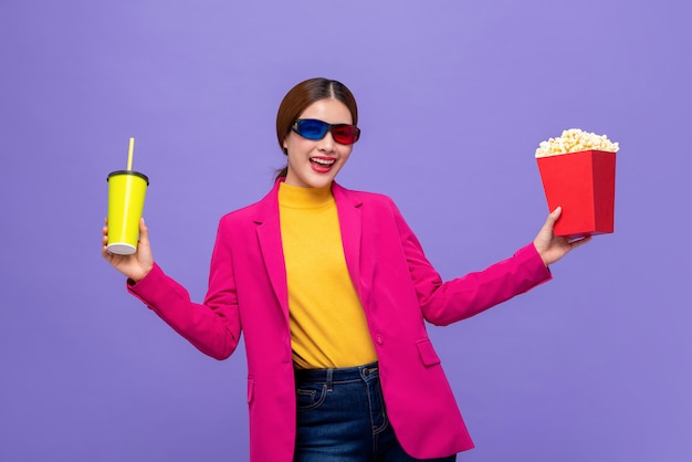 Woman wearing 3d glasses watching movie with drink and popcorn Premium Photo