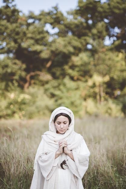 Женщина в библейском халате и молится, когда ее глаза закрыты Бесплатные Фотографии