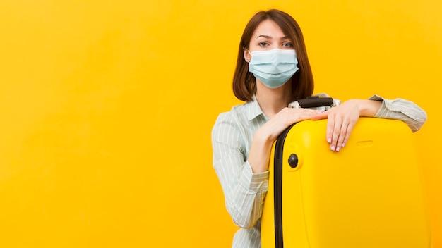 Женщина, носящая медицинскую маску, держа ее желтый багаж Premium Фотографии
