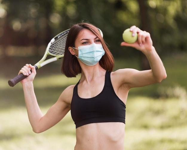Женщина, носящая медицинскую маску во время подготовки к теннисному матчу Бесплатные Фотографии