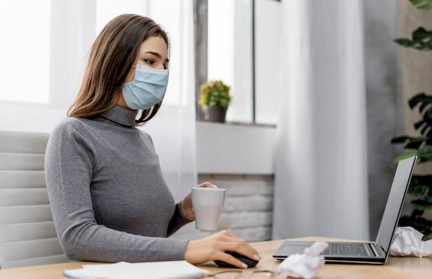 가정에서 일하는 동안 의료 마스크를 쓰고 여자 무료 사진