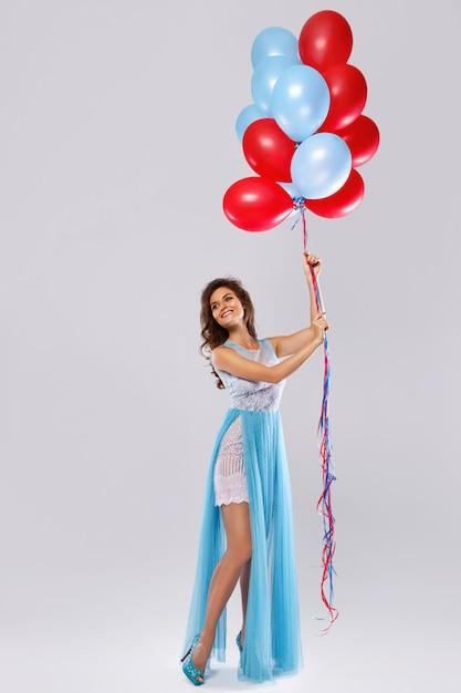 Женщина в красивом платье с большим количеством разноцветных шаров Premium Фотографии