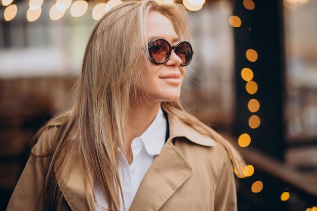 Woman wearing beige coat and walking in the street on christmas Free Photo