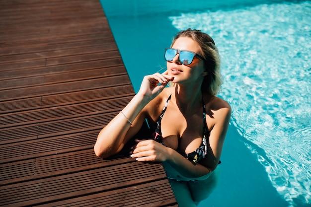 夏の風景のプールサイドで黒いビキニを着ている女性 無料写真