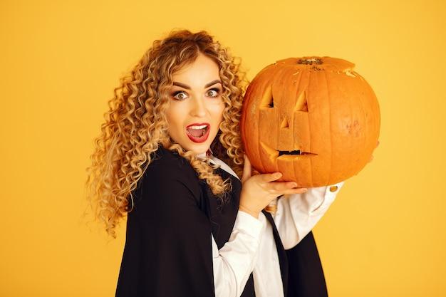 Женщина в черном костюме. дама с хеллоуинским макияжем. девушка стояла на желтом фоне. Бесплатные Фотографии