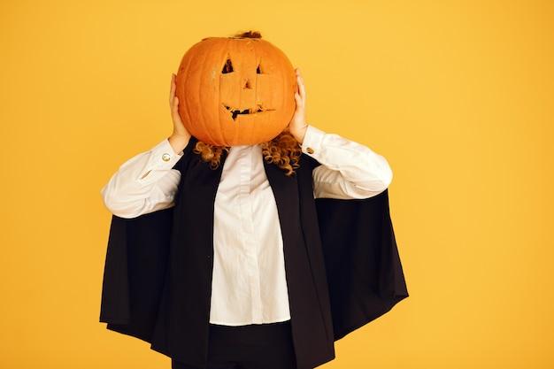검은 의상을 입고 여자입니다. 할로윈 메이크업 레이디. 노란색 배경에 서있는 소녀. 무료 사진