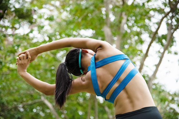 Woman wearing exercise suit, stretching back and body by raise hands up and reach out in the air Premium Photo