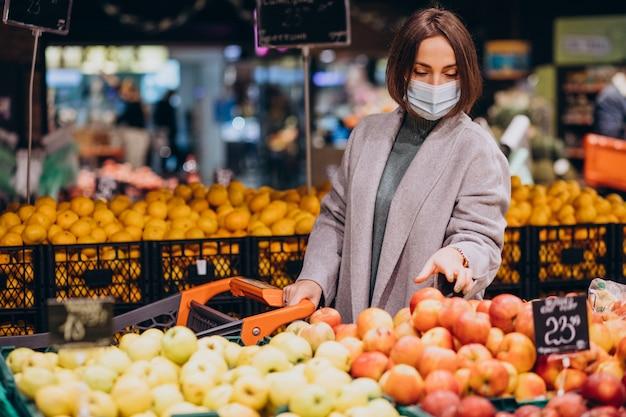 여자 얼굴 마스크를 착용하고 식료품 점에서 쇼핑 무료 사진