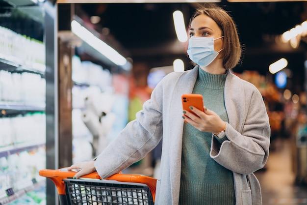 フェイスマスクを着用し、食料品店で買い物をする女性 無料写真