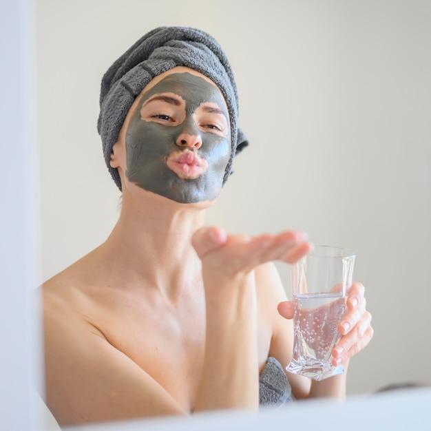 鏡にキスを吹くフェイスマスクを着ている女性 無料写真