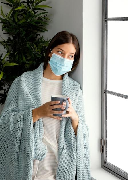 Donna che indossa la maschera per il viso a casa Foto Gratuite