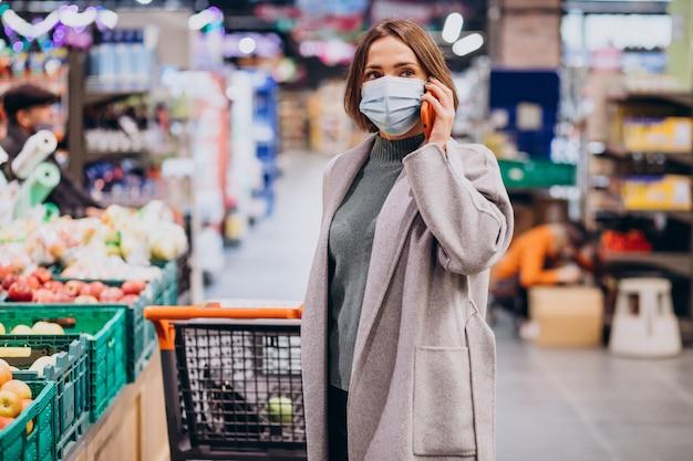 Donna che indossa la maschera per il viso e lo shopping nel negozio di alimentari Foto Gratuite