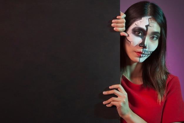 Woman wearing halloween costume behind wall Free Photo