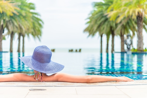 Woman wearing hat in the hotel pool resort Free Photo