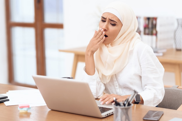 Woman wearing a headscarf sitting tired at work. Premium Photo
