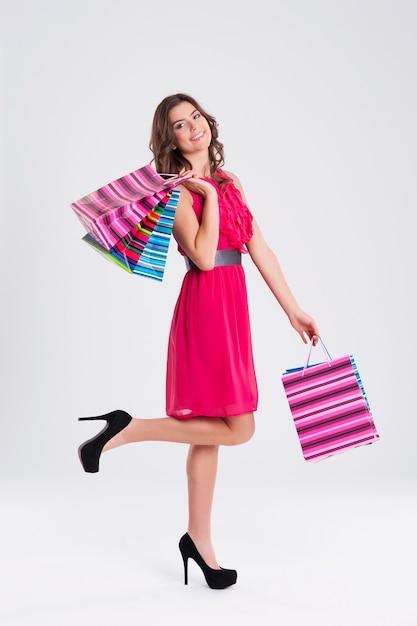 ショッピングバッグを保持しているピンクのドレスを着ている女性 無料写真