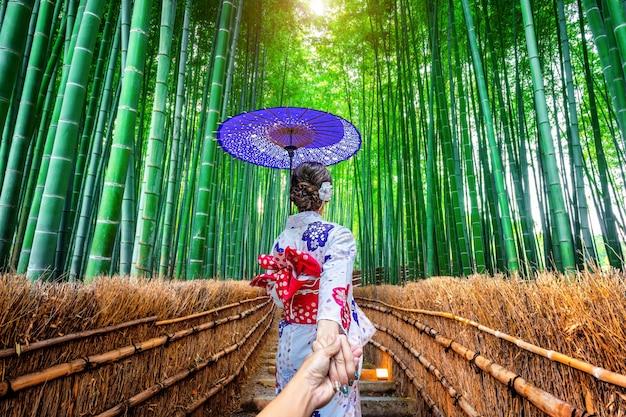 男の手を握って日本の伝統的な着物を着て、京都の竹林に連れて行く女性。 無料写真