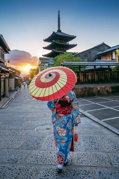 일본 교토의 야 사카 파고다와 산넨 자카 거리에서 우산으로 일본 전통 기모노를 입은 여성. 무료 사진
