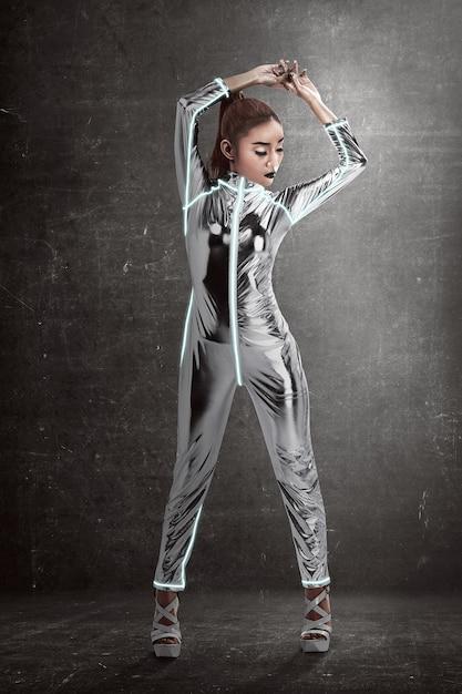 グランジ背景にポーズをとってラテックスジャンプスーツを着ている女性 Premium写真