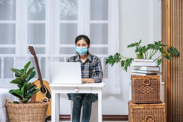 Una donna che indossa una maschera hygiene è seduta alla scrivania con un laptop. Foto Gratuite