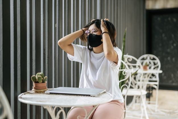 A woman wearing a mask playing a laptop and both hands holding the head Free Photo