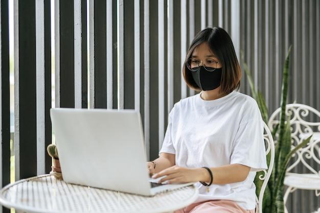 A woman wearing a mask and playing a laptop. Free Photo