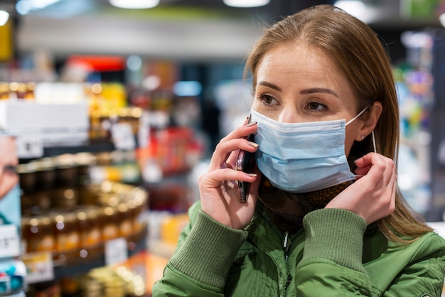 Woman wearing a mask in supermarket Free Photo