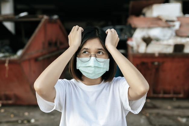 Woman wearing a mask and two hands holding head. Free Photo