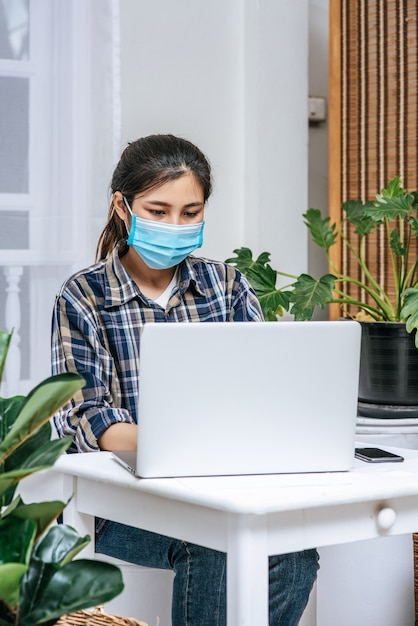 A woman wearing a mask uses a laptop to work. Free Photo
