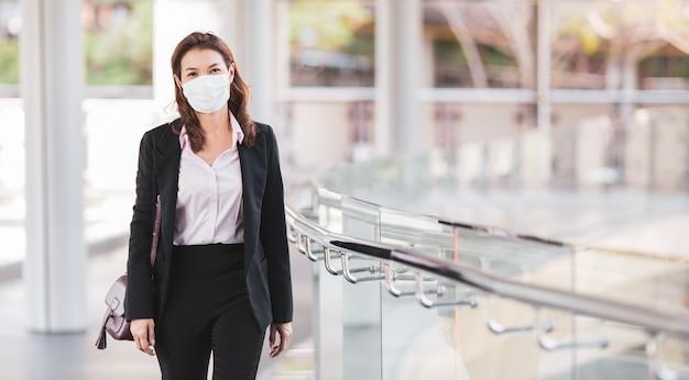 街を歩いてマスクを着ている女性 Premium写真