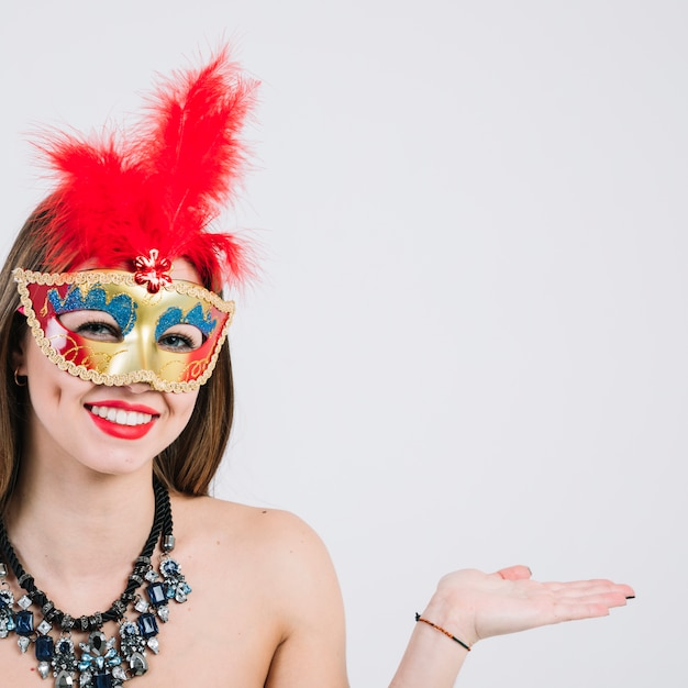Woman wearing masquerade carnival mask and necklace gesturing over white backdrop Free Photo