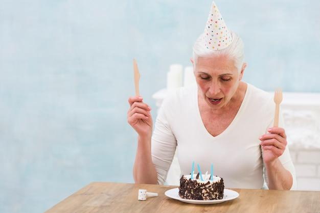 Cappello da portare del partito della donna che tiene coltello e forcella di legno che esaminano la torta di compleanno sulla tabella Foto Gratuite