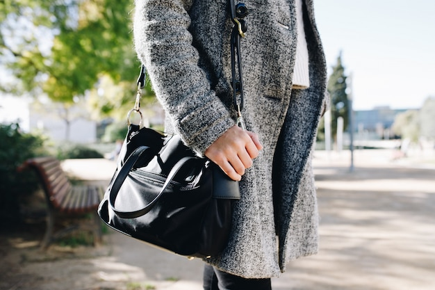 Woman wearing and posing with a coat and purse in autumn collection Premium Photo