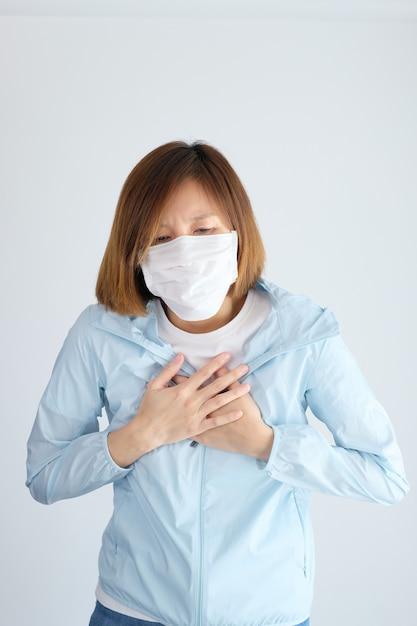 彼女の胸に手を置く防護マスクを着ている女性 Premium写真