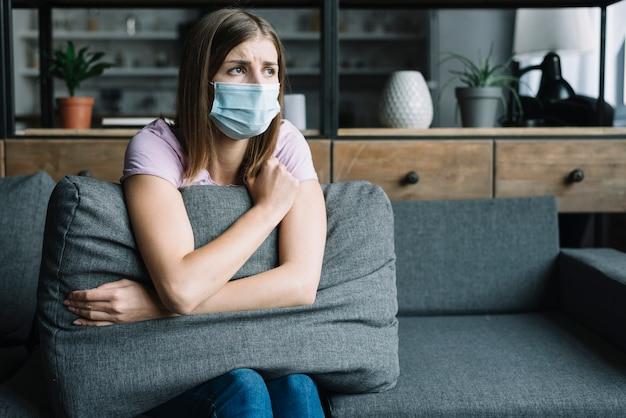Woman wearing protective mask sitting on sofa Free Photo