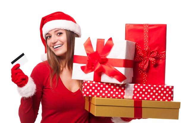 Женщина в шляпе санта-клауса с рождественскими подарками и кредитной картой Бесплатные Фотографии