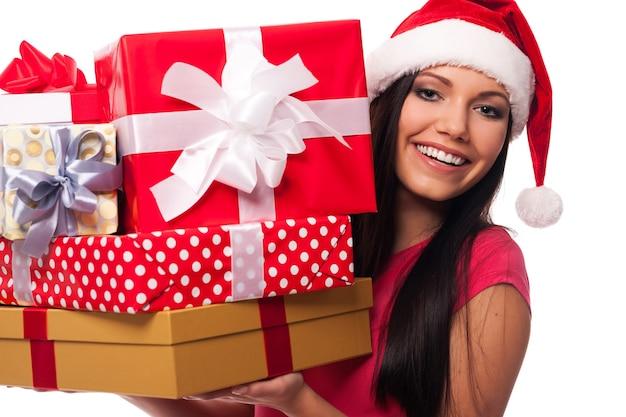 Женщина в шляпе санта-клауса держит стопку рождественских подарков Бесплатные Фотографии