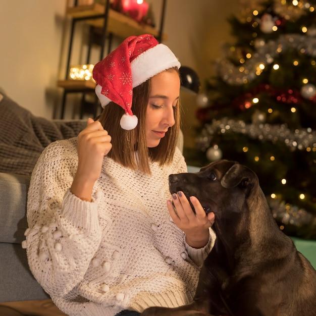 Женщина в шляпе санта-клауса на рождество и ее собака Бесплатные Фотографии