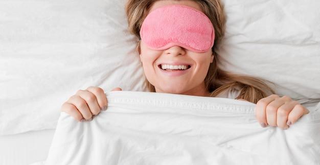 Donna che indossa una maschera per dormire sui suoi occhi e sorrisi Foto Gratuite