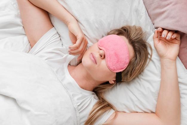 Donna che indossa una maschera di sonno sul suo occhi vista dall'alto Foto Gratuite