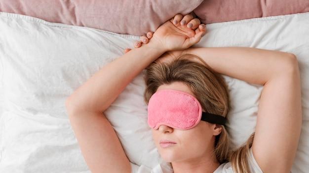 Donna che indossa una maschera per dormire sui suoi occhi Foto Gratuite