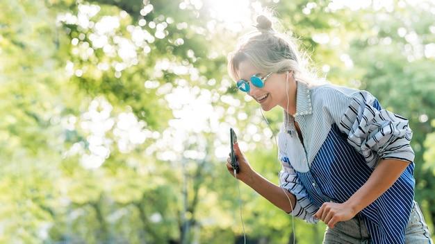 サングラスをかけて音楽を聴く女性 無料写真