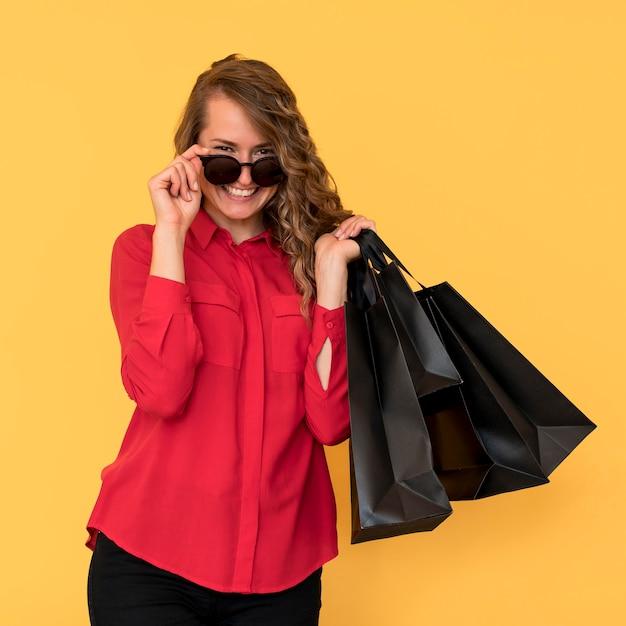Donna che indossa occhiali da sole e tenendo le borse della spesa Foto Gratuite