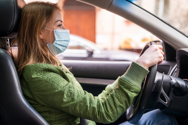 Woman wearing surgical face mask in the car | Free Photo