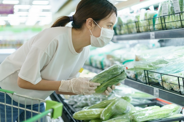 Woman wearing surgical mask and gloves,  choosing vegetables in supermarket after coronavirus pandemic. Premium Photo