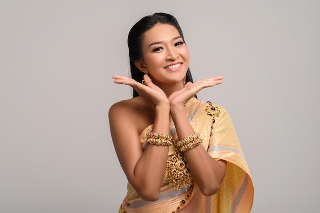 Woman wearing thai dress that made a hand symbol Free Photo