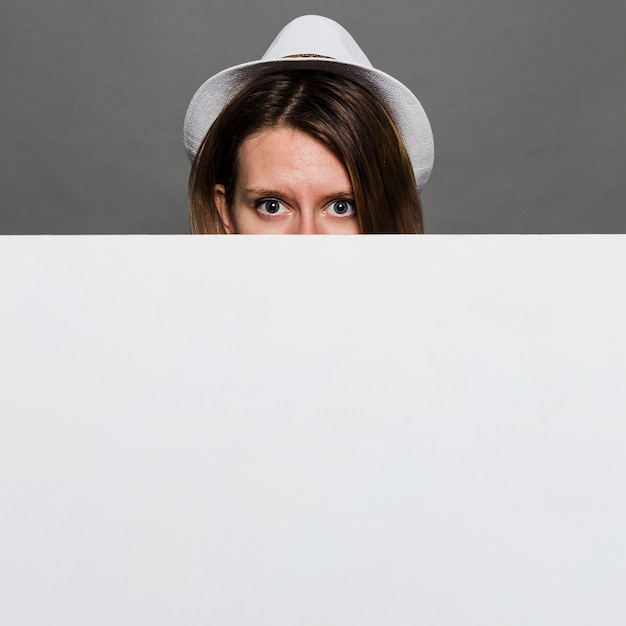 Woman wearing white hat peeking through white blank card against grey wall Free Photo