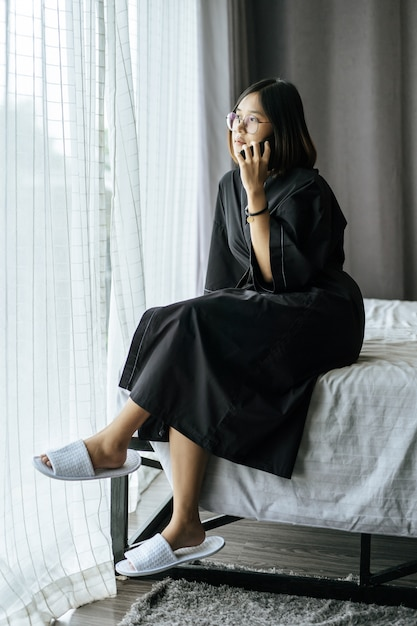 Woman wearing a white shirt, sitting on the bed and talking on the phone. Free Photo