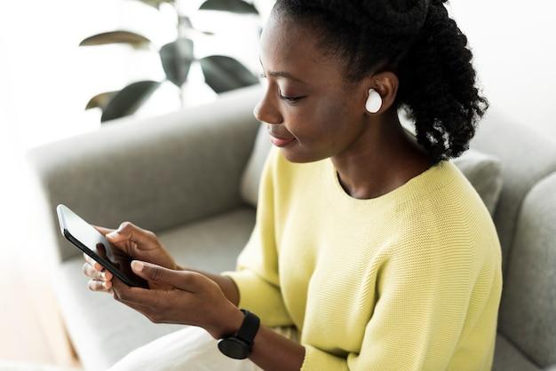 ワイヤレスイヤフォンを着用し、携帯電話を使用している女性 無料写真