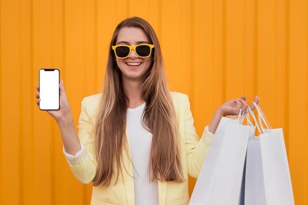 노란색 옷을 입고 전화를 들고 여자 프리미엄 사진